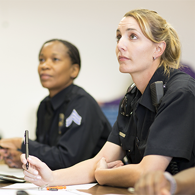 Two uniformed law enforcement officers, one a sergeant, during a briefing.