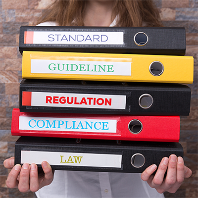 Woman holding a stack of notebooks labelled: Standard, Guideline, Regulation, Compliance, and Law.