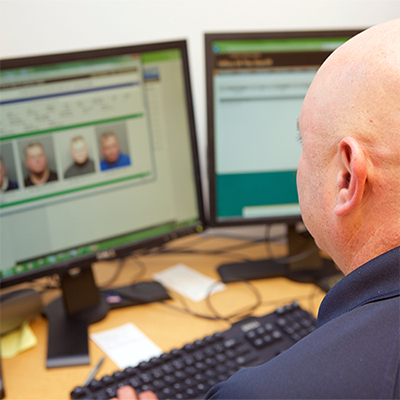Officer looking at mugshots on a computer screen.